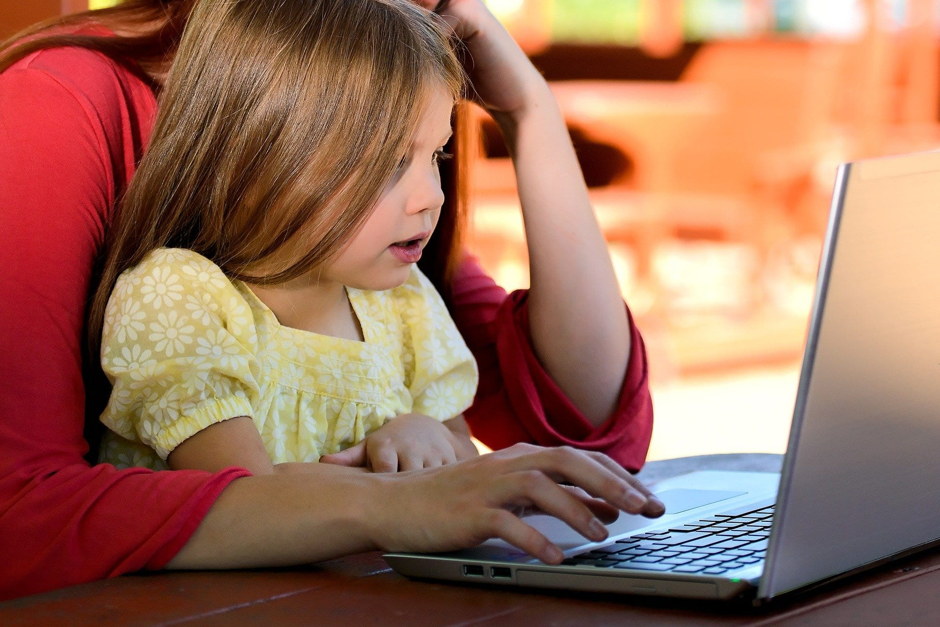 mom and little girl looking at laptop