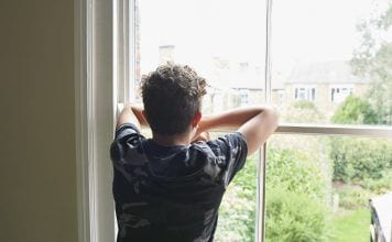 Teenage boy looking out of bedroom window