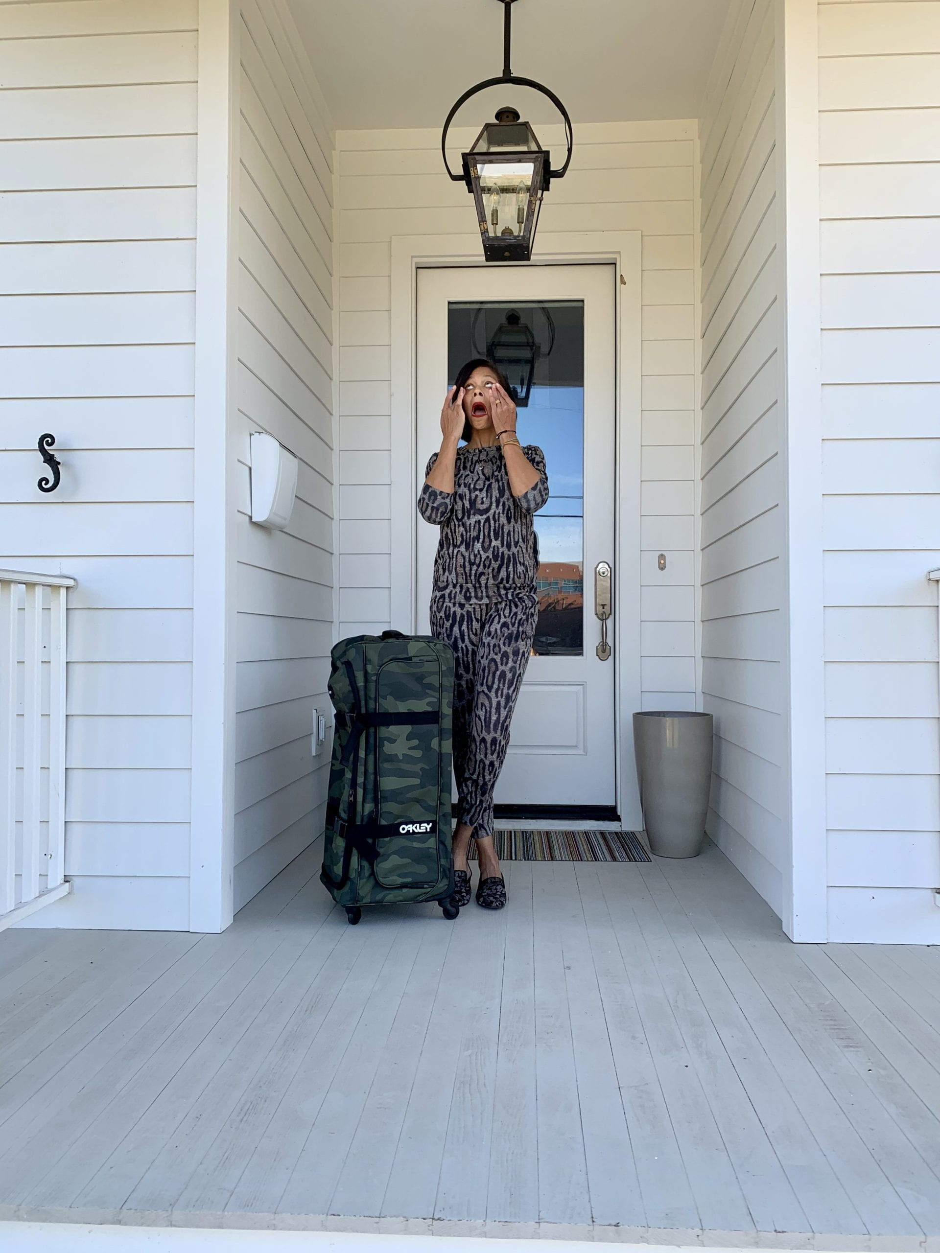 stressed woman on porch with luggage