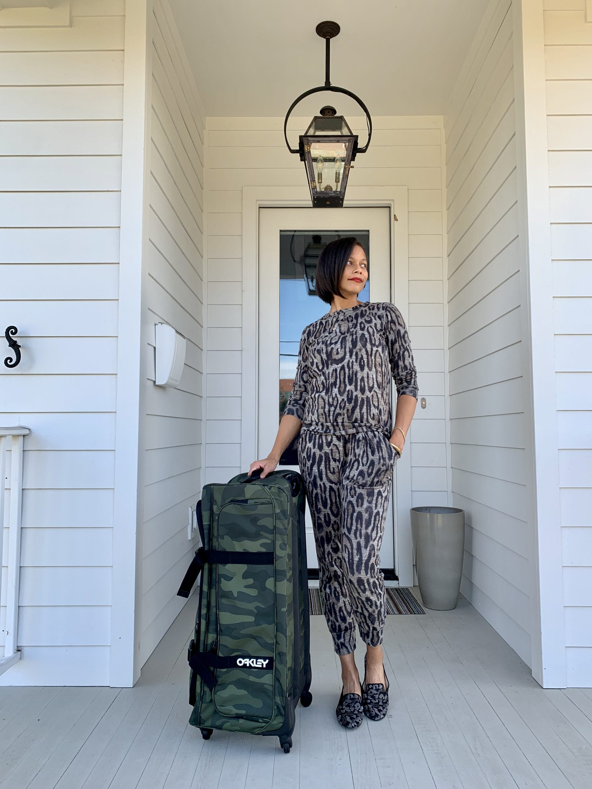 woman standing on porch with luggage