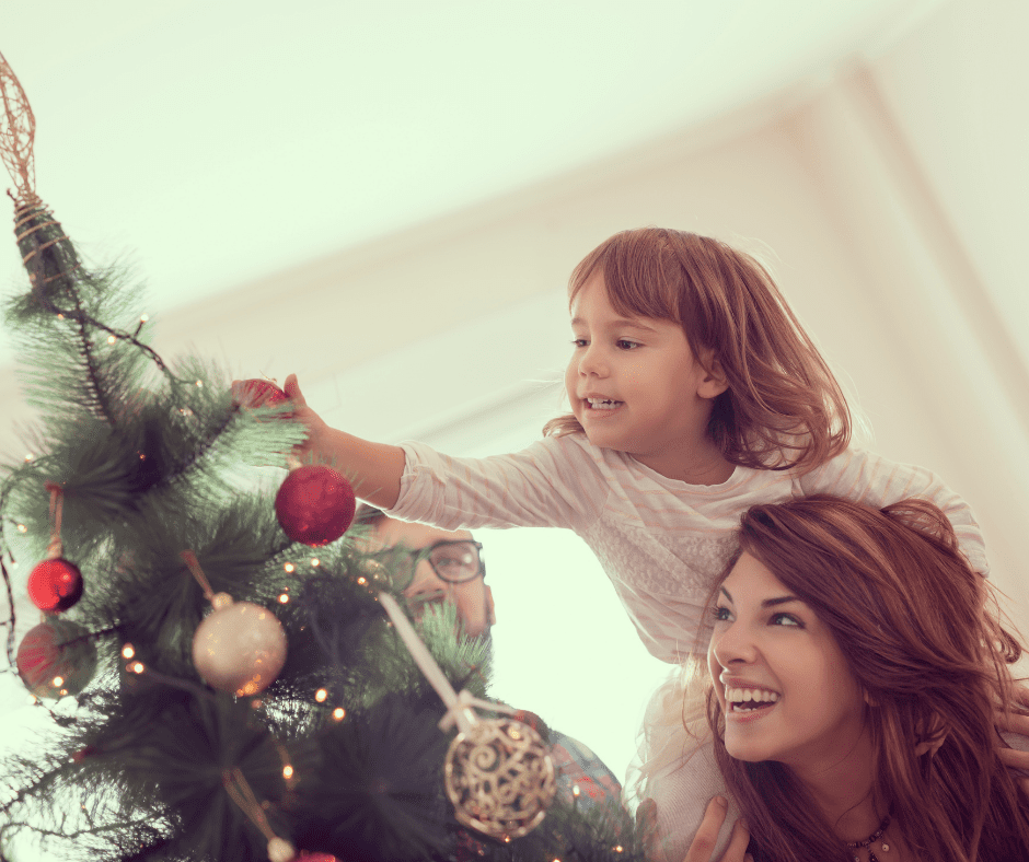 mom and daughter decorating the tree