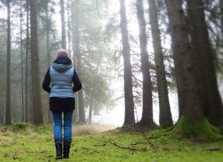 woman walking out of forest