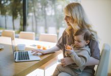 woman at table on laptop holding child eating an orange