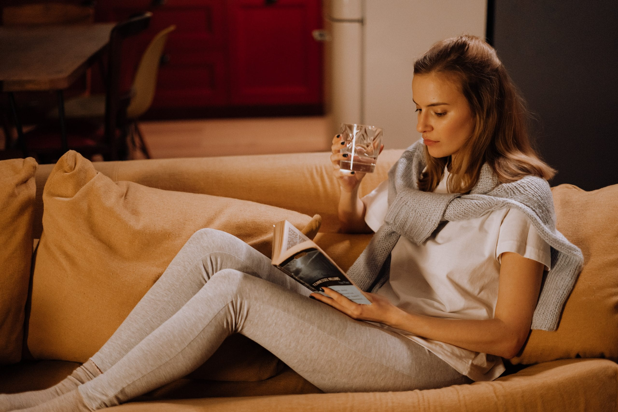 woman reading a book with a glass of water in hand