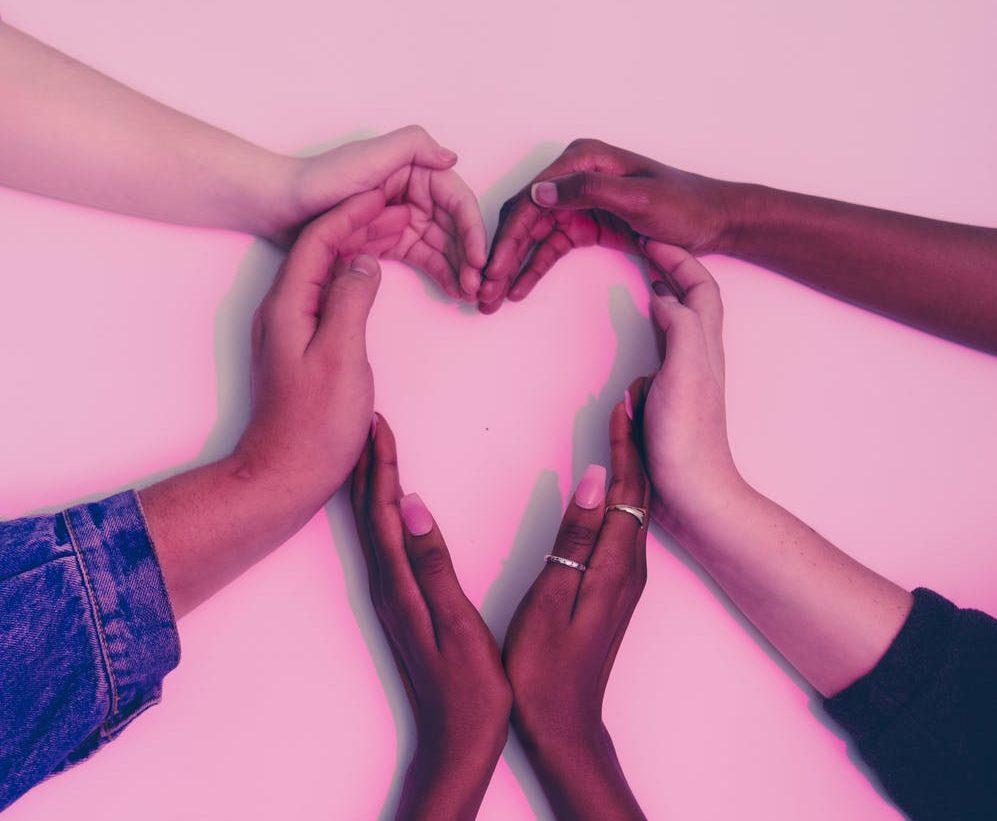 muti race hands in the shape of a heart