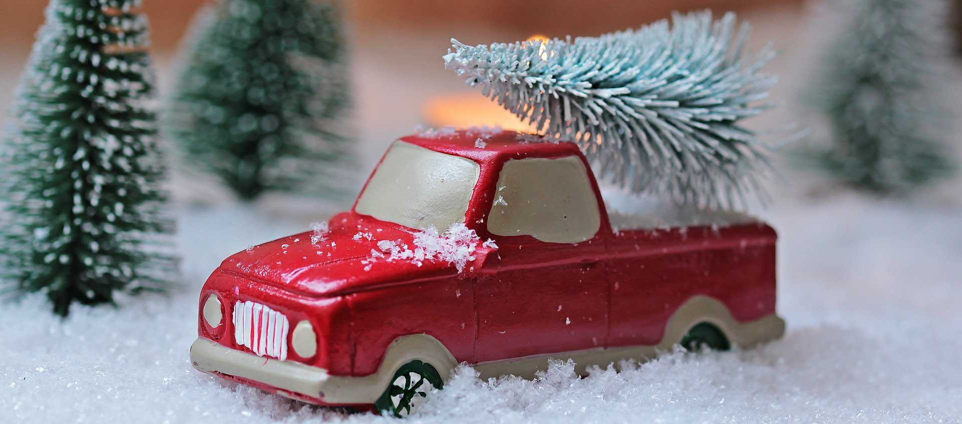 figurine of red truck with Christmas tree in back in snow