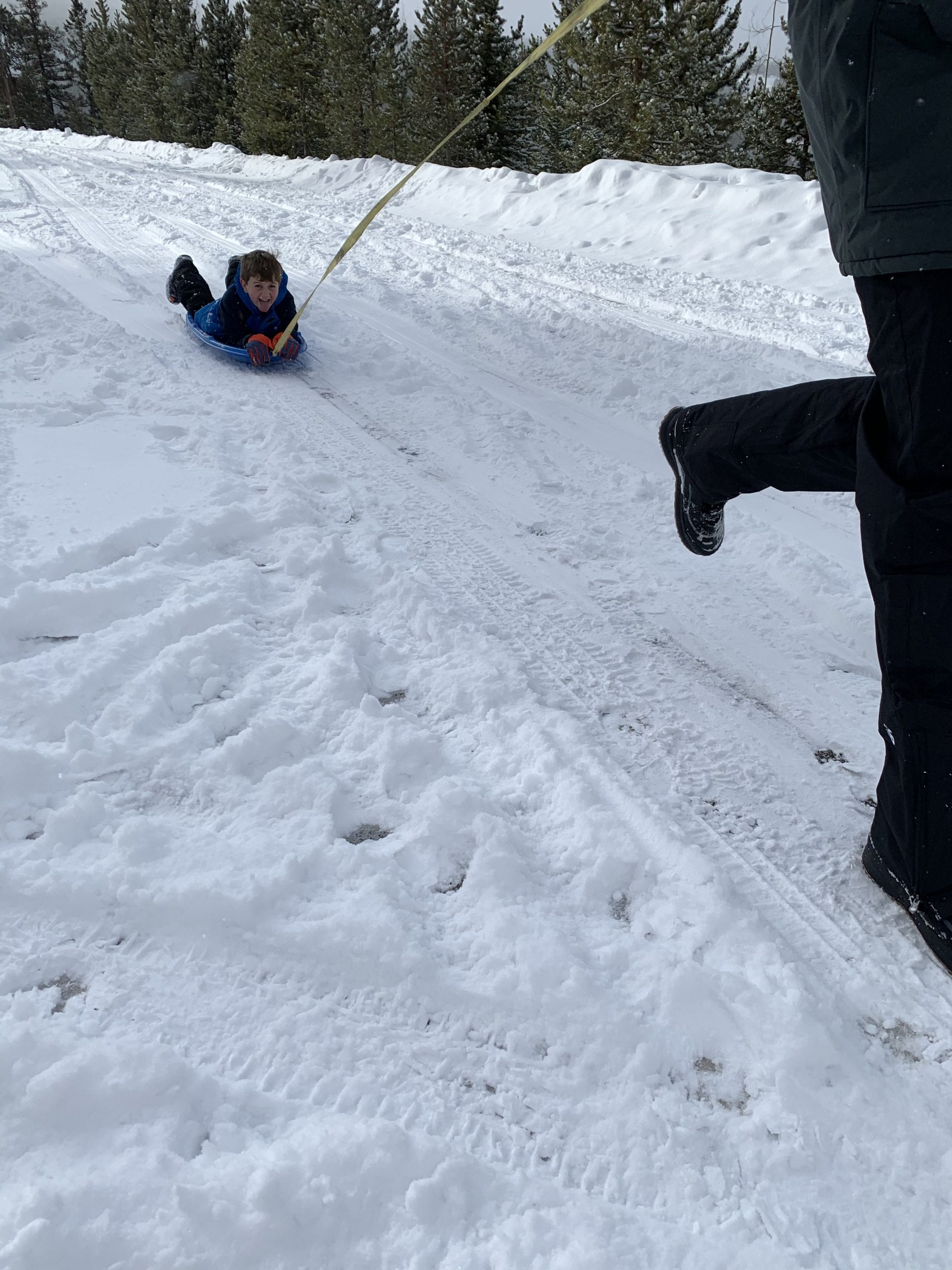 child sledding down mountain in Colorado