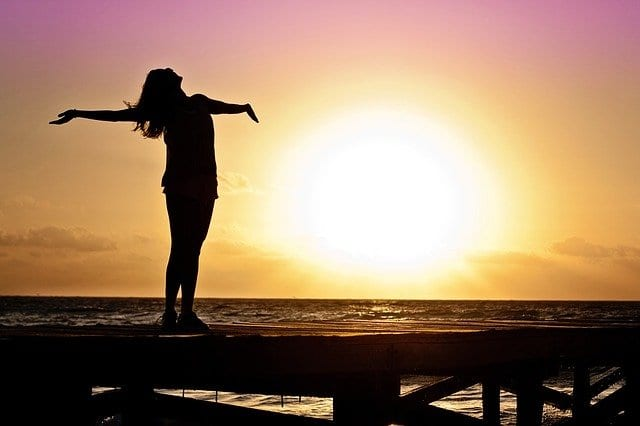 relieved woman standing at sunset with arms wide open